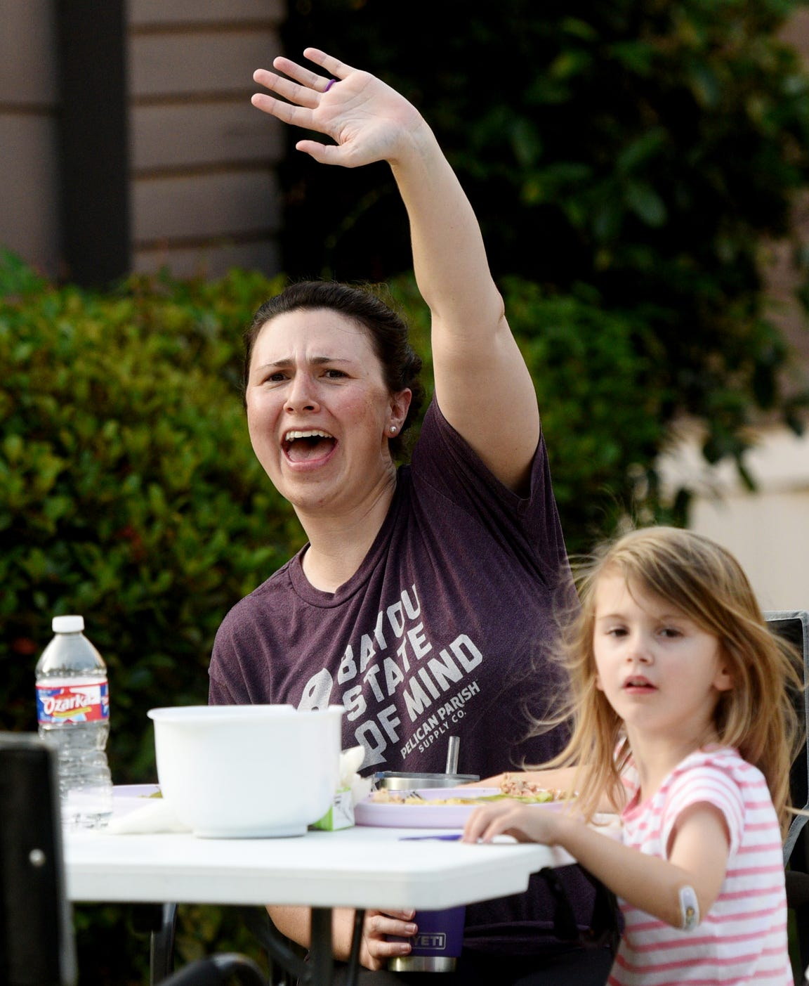 Carrie Osborne waves to a neighbor who drives by during the community dinners on the 700 block of Delaware Street.