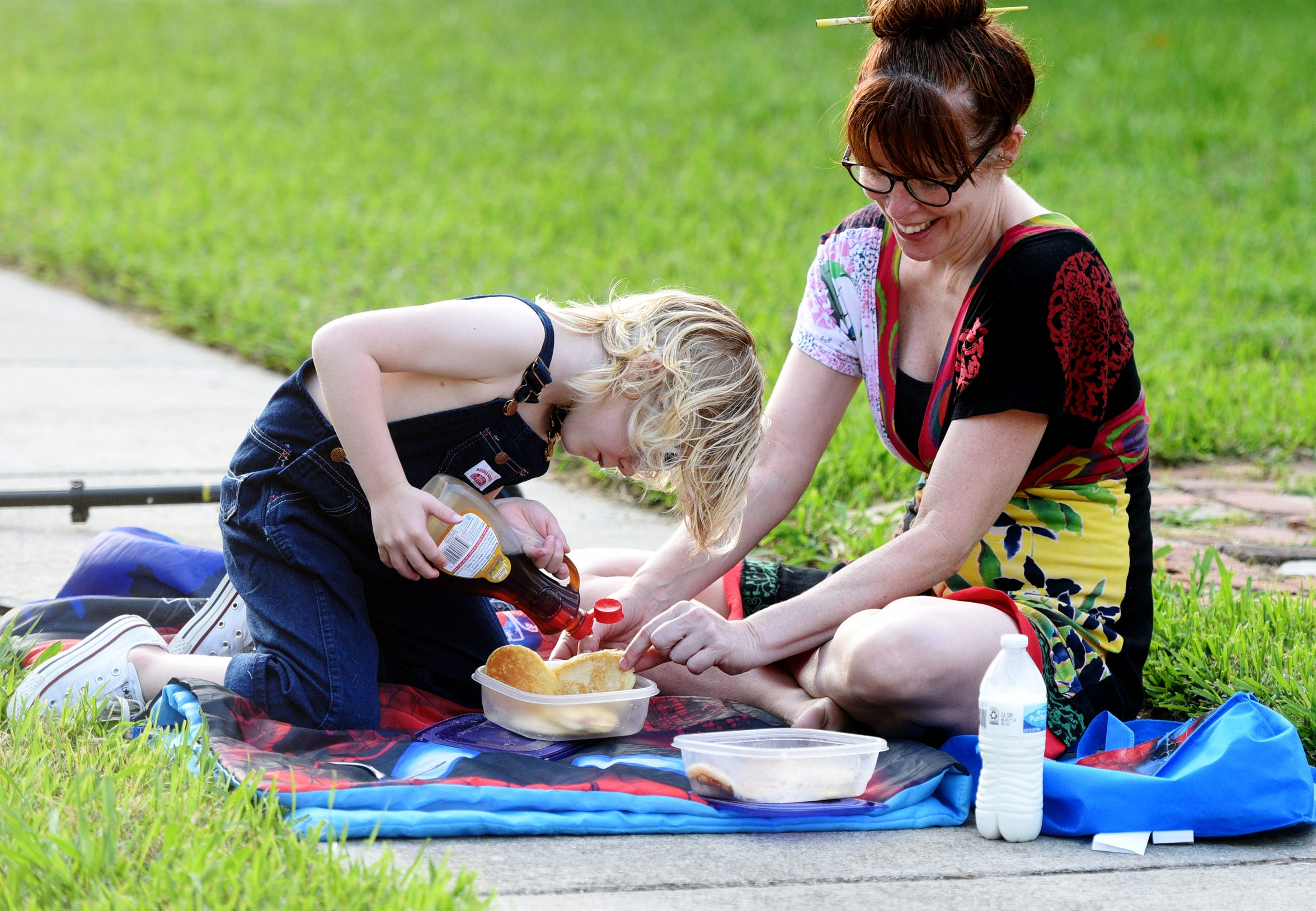 Eli Brasell and her son Motley Brasell picnic on the sidewalk during one of the community dinners on the 700 block of Delaware Street.