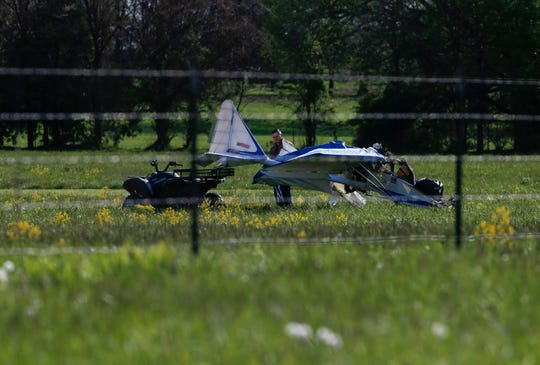 A man tows away the wreckage of an ultralight airplane that crashed on Sunday evening, killing its sole occupant.