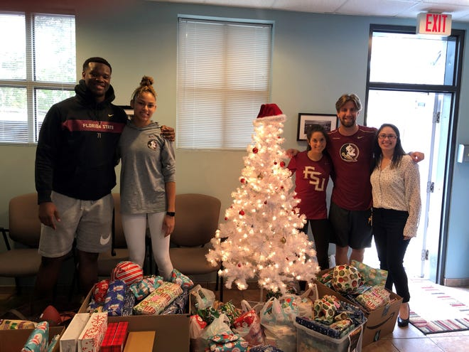 A group of FSU student-athletes including football player Chaz Neal, volleyball player Tiana Jackson and swimmer Paxton Rhoads participate in the Big Bend Holiday Angels program.