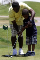 05/14/2010 Former NFL player Ray Mickens, an Andress High School graduate,  shows his son, Preston Mickens, 5, how to putt during the seventh annual Ray Mickens Celebrity Weekend golf tournament Friday at Painted Dunes Desert Golf Course. Mickens will host a free football camp at 10 a.m. today at Andress.