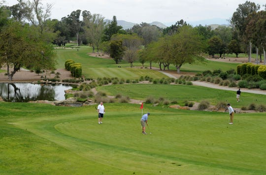Players putt on the 18th green at Los Robles Greens Golf Course in Thousand Oaks on Monday. County golf courses were allowed to reopen with restrictions, which include no motorized carts.