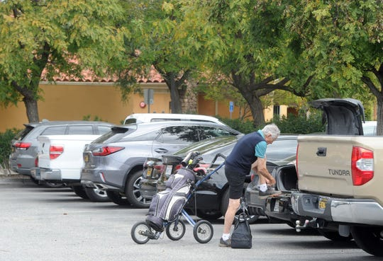 A golfer puts his shoes on in the parking lot at Los Robles Greens Golf Course in Thousand Oaks on Monday. County golf courses were allowed to reopen with restrictions, which include no motorized carts.