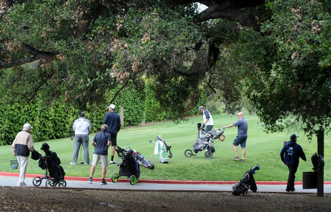 Players tee off on the first hole of Los Robles Greens Golf Course in Thousand Oaks on Monday. County golf courses were allowed to reopen with restrictions, which include no motorized carts.