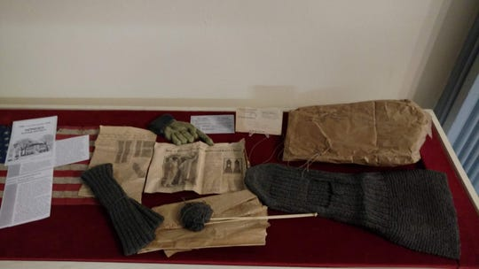 Gloves knit by Somers women to aid in the war effort for World War I. Also pictured are articles with knitting instructions.