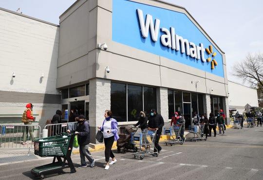 Gente usando mascarillas y guantes esperan para entrar a una Walmart.
