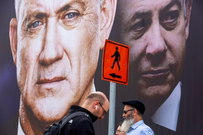People walk past an election campaign billboard for the opposition Blue and White party, led by Benny Gantz, left, in Ramat Gan, Israel, on Feb. 23.