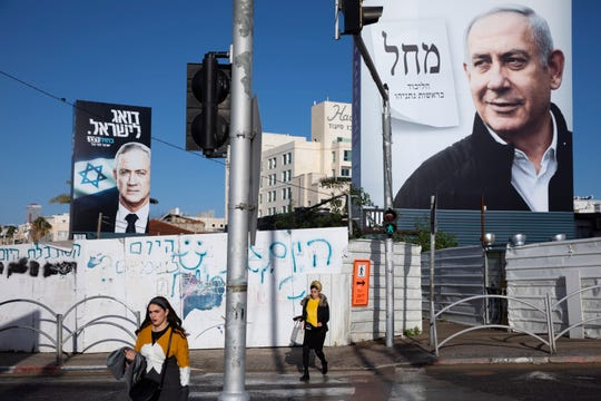 In this March. 1, 2020 file photo, people walk next to election campaign billboards showing Israeli Prime Minister Benjamin Netanyahu, right, and Benny Gantz, left, in Bnei Brak, Israel.