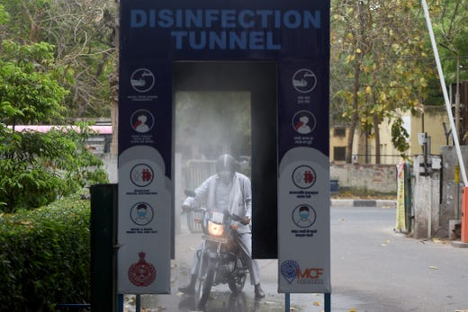 An employee of the municipal corporation drives through a disinfection tunnel outside their office building during a government-imposed nationwide lockdown as a preventive measure against the COVID-19 coronavirus in Faridabad, India on April 20, 2020.