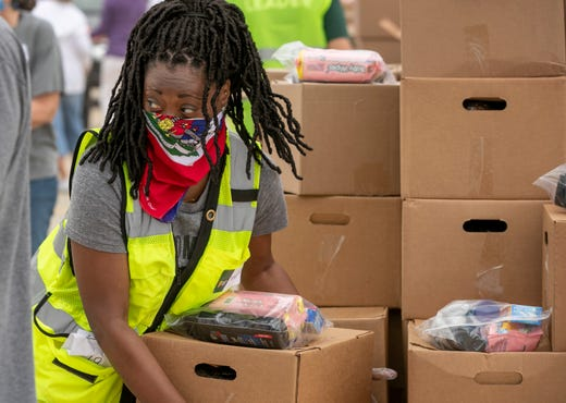 Fadia Joseph volunteers at a Central Texas Food Bank drive-through distribution at Del Valle High School in Austin, Texas, on April 20, 2020.  About 100 volunteers distributed nonperishable food and toiletries to thousands of people who have been affected by the coronavirus pandemic.