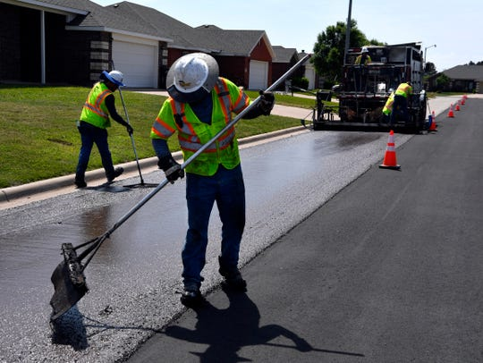 Road crews seal coat part of Cotton Candy Road Tuesday.