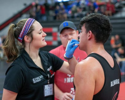 An athletic trainer works during a wrestling match.
