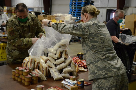 Master Sgt. John Watson, left, and Senior Airman Eran Mikolowski sort food for family baskets on Tuesday.  Trace Christenson/The Enquirer