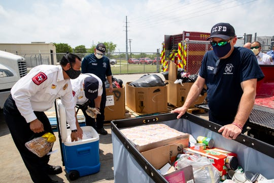 Corpus Christi firefighters and chiefs unload bags of food from a fire truck as the departments food to the Coastal Bend Food Bank on Tuesday, April 21, 2020.