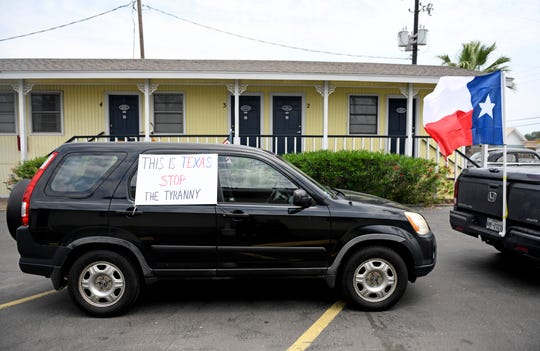 """A """"This is Texas Stop the Tyranny"""" sign is during during the driving protest, Tuesday, April 21, 2020, in Port Aransas. The protest opposes the mayoral declaration that prohibits certain kinds of business activity to prevent the spread of the coronavirus."""