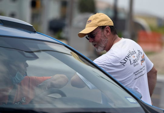 Amelia's Landing co-owner Jay Honeck bumps elbows with drive protesters, Tuesday, April 21, 2020, in Port Aransas. The protest opposes the mayoral declaration that prohibits certain kinds of business activity to prevent the spread of the coronavirus.