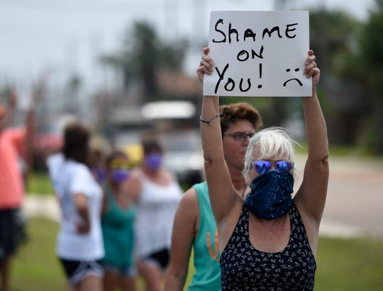 """Renee Garland holds a """"shame on you"""" sign during the counter protest, Tuesday, April 21, 2020, in Port Aransas. """"We don't think it's safe to re-open, not at the risk of people's health,"""" Garland says."""