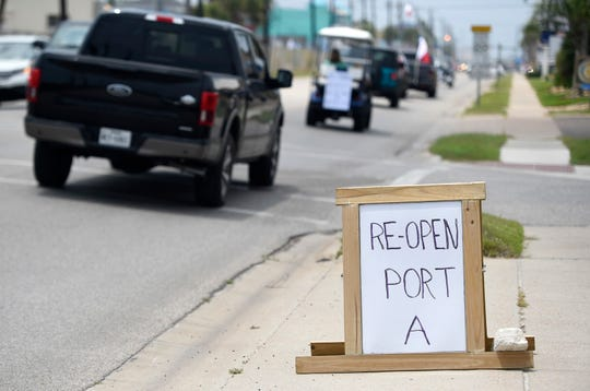 "A ""re-open Port A"" sign is seen during the driving protest, Tuesday, April 21, 2020, in Port Aransas. The protest opposes the mayoral declaration that prohibits certain kinds of business activity to prevent the spread of the coronavirus."