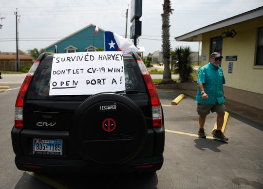 "A ""Survived Harvey Don't let CV-19 Win! Open Port A!"" sign is seen before the driving protest, Tuesday, April 21, 2020, in Port Aransas. The protest opposes the mayoral declaration that prohibits certain kinds of business activity to prevent the spread of the coronavirus."