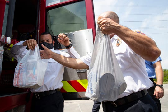 Corpus Christi Fire Battalion Chief Tony Perez helps unload bags of food from a fire truck as the departments food to the Coastal Bend Food Bank on Tuesday, April 21, 2020.