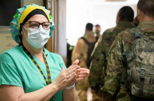 Cheryl Ozalas, a residential nurse at Salem Medical Center, on Monday welcomes soldiers who will assist in treatment of COVID-19 patients at the Salem facility.