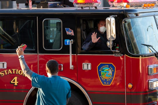 A Winslow Township engine passes as a caravan of first responders parade by Cooper University Hospital in support of healthcare workers Monday, April 20, 2020 in Camden, N.J.