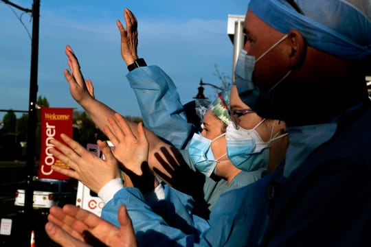 Healthcare workers from the operating room wave as a caravan of first responders parade by Cooper University Hospital Monday, April 20, 2020 in Camden, N.J.