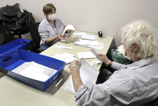 Absentee ballot clerks Kathy Morland, left, and Dennis Miller, right, remove stubs from absentee ballots at the Franklin County Board of Elections, 1700 Morse Road on Tuesday, April 21, 2020. The stubs are taken off before the ballot can be placed in the ballot scanner.