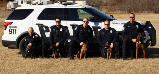 The Altoona Police Department officers who are serving as handlers for the puppies during their training pose with the dogs alongside Capt. Todd Trobaugh and police dog Judge.