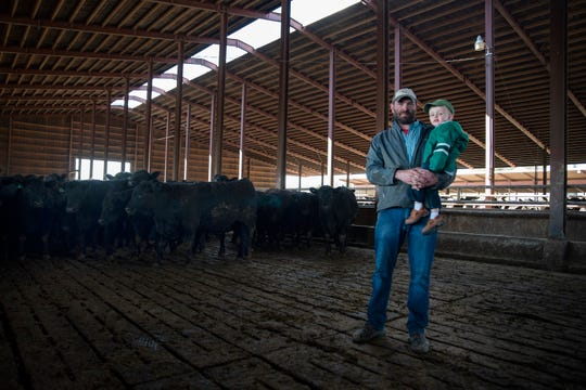Justin Reiter poses in a cattle barn with his son Eddie at his home on April 21, 2020 in Bernard, Iowa. Reiter's cattle farm has been passed down for over 175 years, and is now seeing losses of about $300 per head of cattle due to economic effects of the coronavirus.