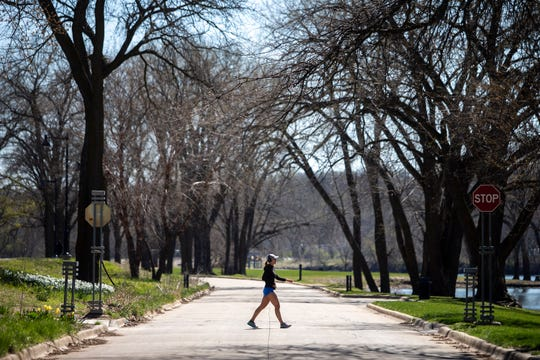 A woman crosses the road through Gray's Lake that has now been closed to drivers to allow people to more easily keep a social distance on Tuesday, April 21, 2020, in Des Moines.