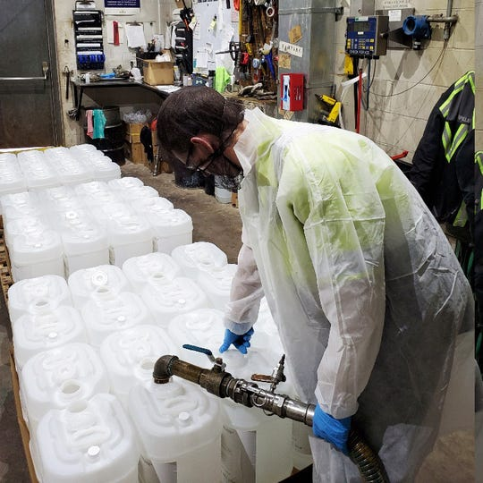 A Haviland Enterprises employee works to make hand sanitizer in partnership with Plymouth Technology, Inc. at their Grand Rapids facility.