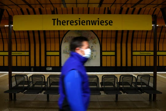 A man wearing a protection mask as he pass the subway sign 'Theresienwiese', the Oktoberfest beer festival area, in Munich, Germany, Tuesday. Bavarian state governor Markus Soeder and Munich mayor Dieter Reiter announced at a news conference that the Oktoberfest is cancelled this year because the coronavirus outbreak.