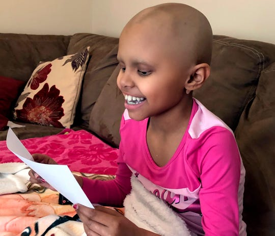 In this April 1, 2020 photo provided by The Valerie Fun, cancer patient Sophie Chhowalla, 8, reads an uplifting note from stranger Sarah Schneider while resting at her home in Berkeley, N.J.