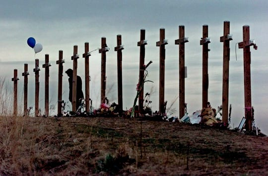 A woman stands among crosses posted on a hill in 1999 above Columbine High School in Littleton, Colo., in remembrance of the people who died during a school shooting on April 20, 1999.
