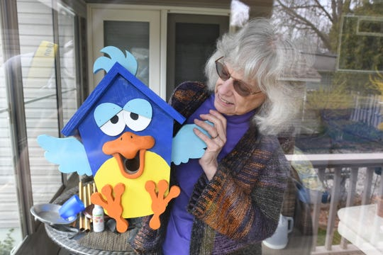Margaret Neumann of Waterford shows off a custom birdhouse on her enclosed back porch as she is riding out the COVID-19 quarantine alone on Tuesday, April 21, 2020.