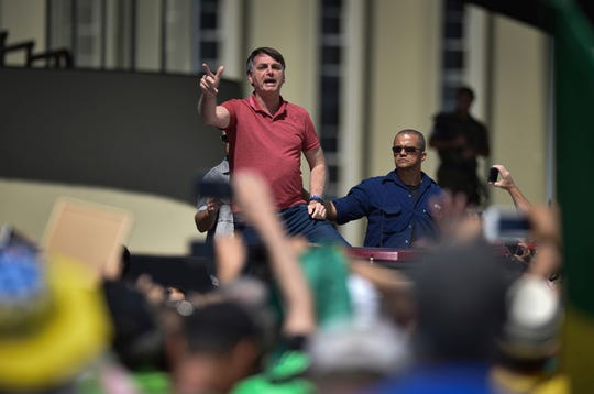 Brazil's President Jair Bolsonaro speaks to supporters during a protest in front of the army's headquarters during the Army day, amid the new coronavirus pandemic on Sunday. Bolsonaro came out in support of a small protest Sunday that defended military intervention, infringing his own ministry's recommendations to maintain social distancing and prompting fierce critics.