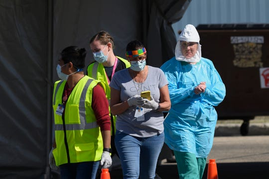 Medical workers administer drive-up COVID-19 tests outside the Sanford Worthington Clinic on Saturday in Worthington, Minn. The state has sent a team to ensure safe conditions in the southwestern Minnesota city, where multiple people have tested positive at a meatpacking plant.