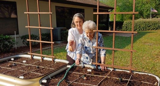 In this April 12, 2020 photo, Brenda Flowers, left, and 96-year-old Lorraine Tyree, water their plants in Crystal River, Fla.