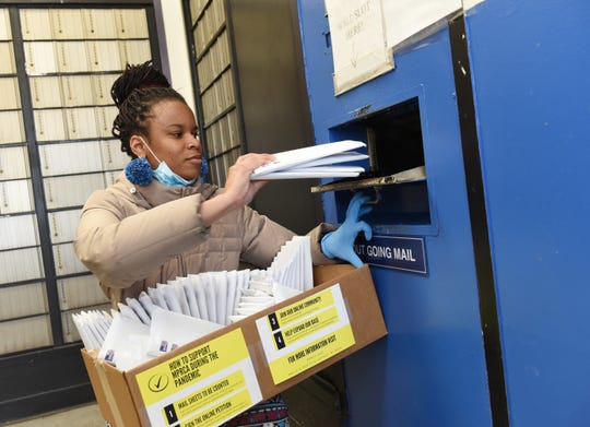 """Amani Sawari, 25, drops off petitions in the mail at Lathrup Village Post Office to supporters for a ballot initiative to restore """"good time"""" credits to the prison system for early release of prisoners."""