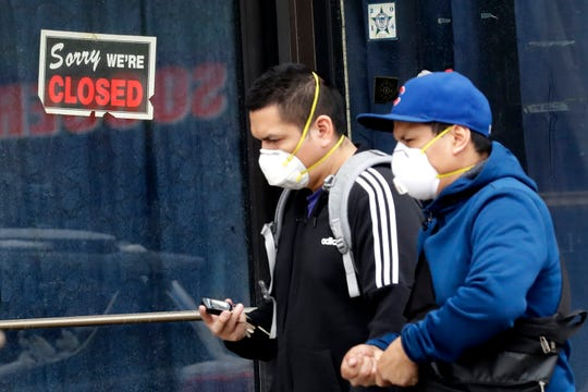 FILE - In this April 15, 2020 file photo, two people walk past a closed sign at a retail store in Chicago.  The Small Business Administration reports it had a potential data breach last month in its website that handles disaster loan applications.