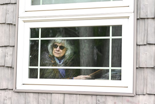 Margaret Neumann looks out her bedroom window in her Waterford home where she has been riding out the COVID-19 quarantine alone.