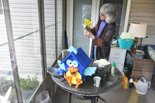 Margaret Neumann works on a project on her enclosed back porch as she is riding out the COVID-19 quarantine alone in her Waterford home.