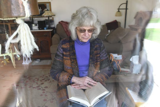 Margaret Newman of Waterford reads a book from the living room in her Waterford home where she has been riding out the COVID-19 quarantine alone, Tuesday, April 21, 2020.