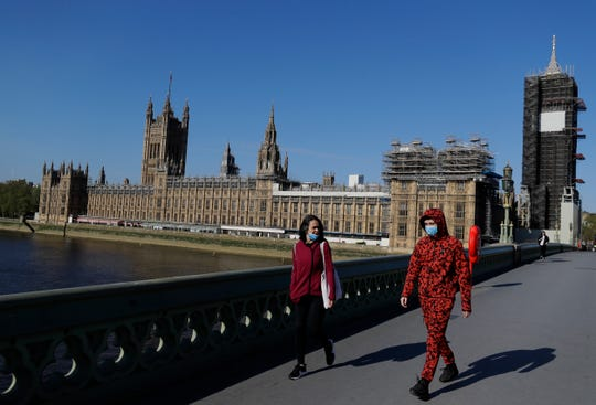 People wear masks as they walk near Britain's Houses of Parliament as the country is in lockdown to help curb the spread of coronavirus, in London, Tuesday.