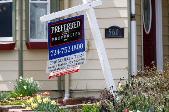 A real estate company sign marks a home for sale, Thursday, April 16, 2020, in Harmony, Pa.