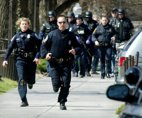 Blacksburg police officers run from Norris Hall during a shooting April 16, 2007, on the Virginia Tech campus in Blacksburg, Virginia.