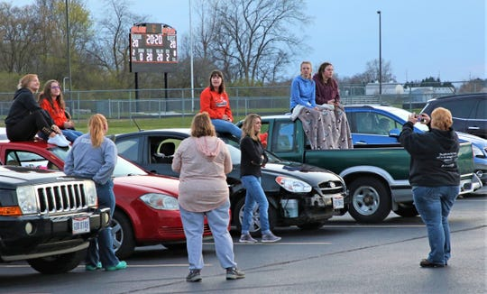 """Students, parents and teachers gathered in the parking lot of Gibsonburg High School for """"Shine Your Lights For Our 2020 Seniors"""" event Monday night. The lights were turned on at 8:20 p.m. at high school stadiums throughout the area for 20 minutes."""