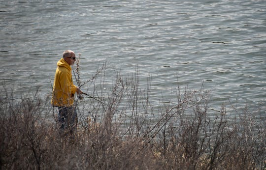A man fishes from the banks at Horsetooth Reservoir in Fort Collins, Colo. on Monday, April 20, 2020.