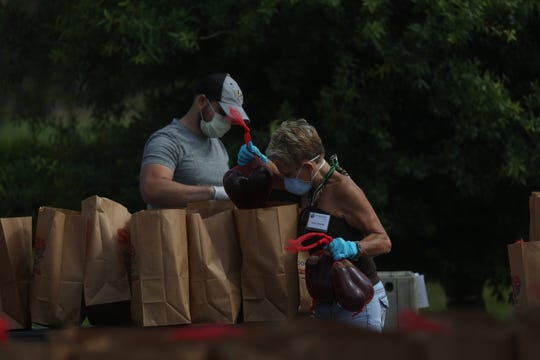 Employees and volunteers for the Harry Chapin Food Bank work a mobile food pantry in Immokalee. The food bank has been delivering between 500-600 pre-packaged meals and vegetables to numerous sites throughout Southwest Florida during the COVID-19 pandemic.